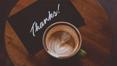 Thank you note on table next to cup of coffee