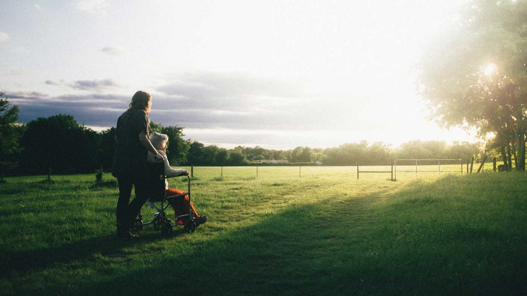Elderly woman in a wheelchair being pushed by a carer through a field