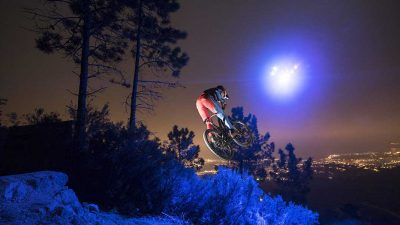 Downhill mountain biker rides full throttle at night with only a drone to guide the way