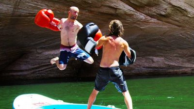 Duo challenged to crazy boxing match on a stand up paddle board…being towed by a boat