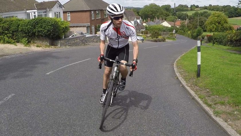 Road cyclist wearing the Coros SafeSound Road helmet while climbing a hill