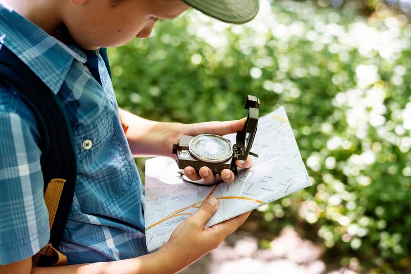 Boy using a map and compass to navigate