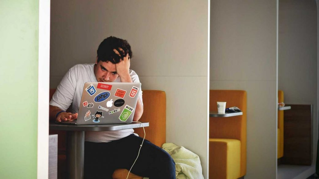 Man trying to concentrate in front of a laptop