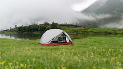 Man camping below a fog covered mountain