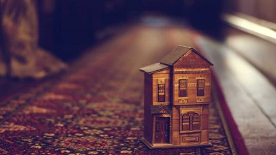 Wooden miniature house on red carpet