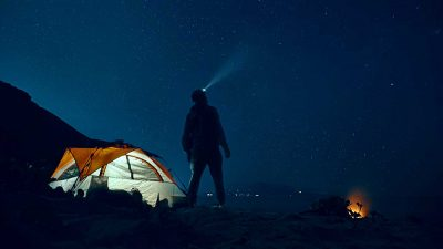 Man standing beside a tent, wearing a headlamp and looking up at a starry night sky