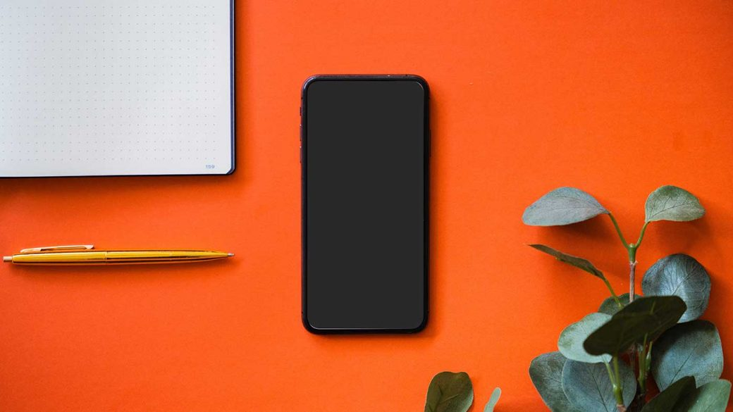 Black mobile phone on orange surface