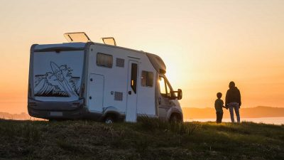 Two campers standing next to RV looking at sunset