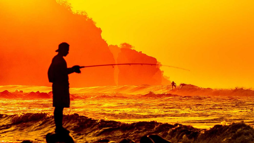 Silhouette of a man fishing at the beach during sunset
