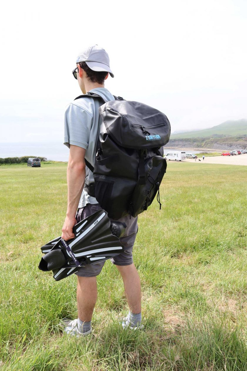 Looking to the left and carrying the DryTide 50L waterproof backpack whilst holding a pair of flippers