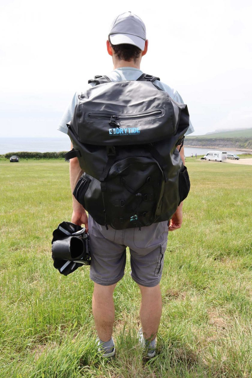 Looking out to sea and carrying the DryTide 50L waterproof backpack whilst holding a pair of flippers