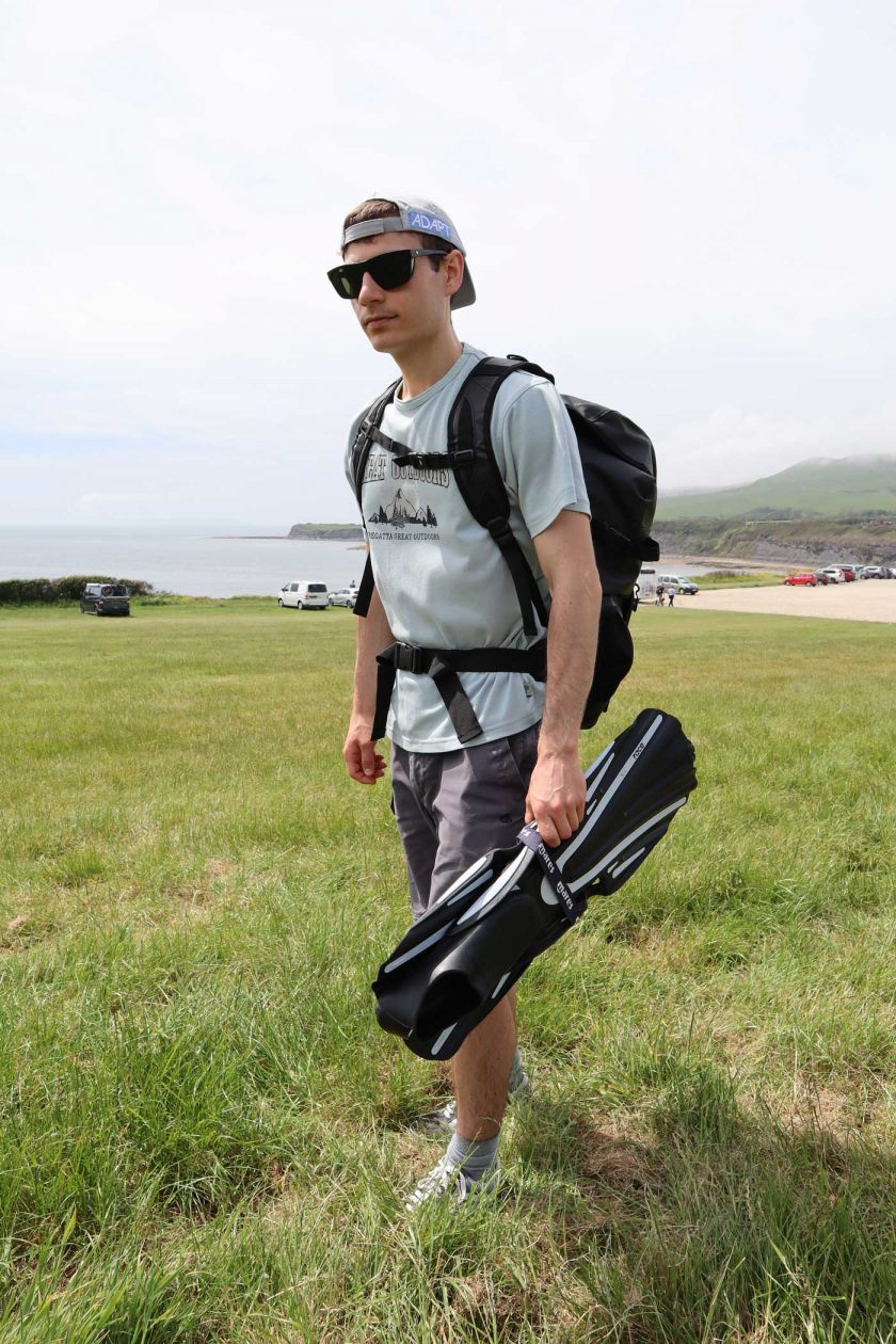 Carrying the DryTide 50L waterproof backpack whilst holding a pair of flippers