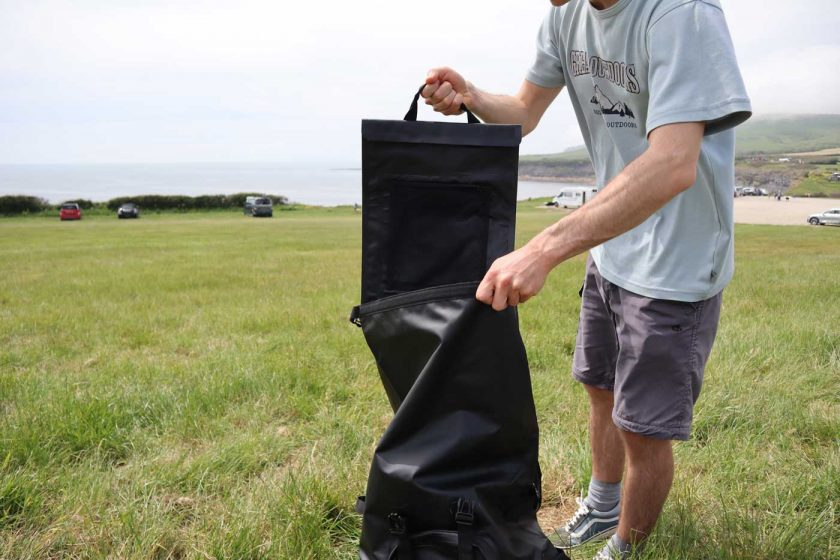 Removing the laptop sleeve from the DryTide 50L waterproof backback for easy access