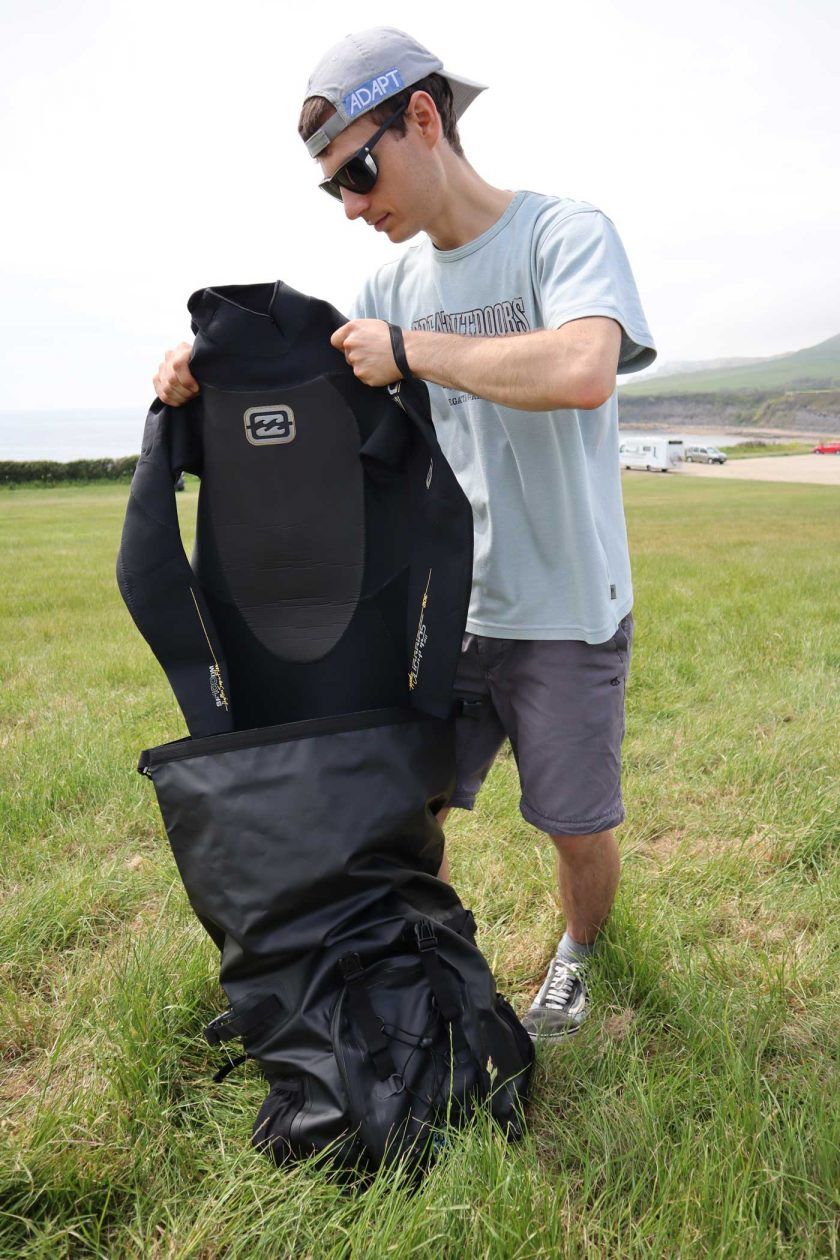 Pulling a wetsuit out of the DryTide 50L waterproof backpack