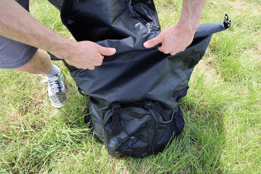 Closing the main compartment of the DryTide 50L waterproof backpack using the roll-top closure