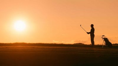 Silhouette of a man playing golf with a sunset in the background