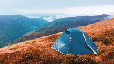Tent pitched on mountain during autumn with tree covered mountains in background