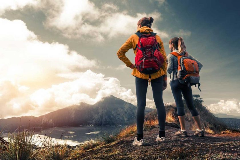 Two female hikers at the top of a mountain looking at a lake below