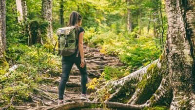 Woman solo hiking on a forest trail