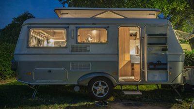Caravan parked next to tree under a starry night sky
