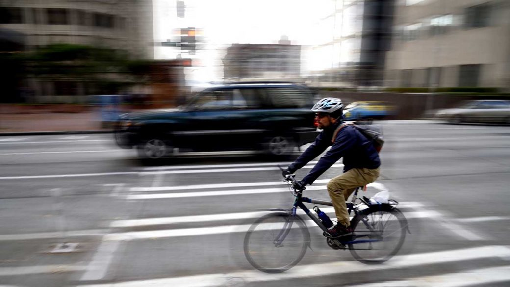 Bike commuter wearing helmet and riding on a busy city road