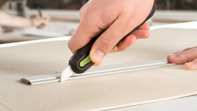 Person using a metal ruler and an auto-retractable utility knife to precision cut cardboard