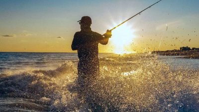 Fisherman standing knee-deep in the sea while fishing for bass at sunset