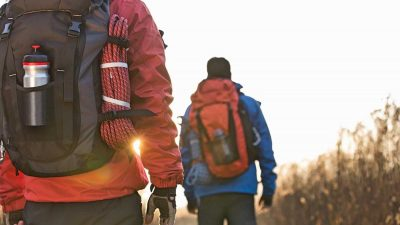 Two hikers wearing winter hiking gear and carrying backpacks with rope