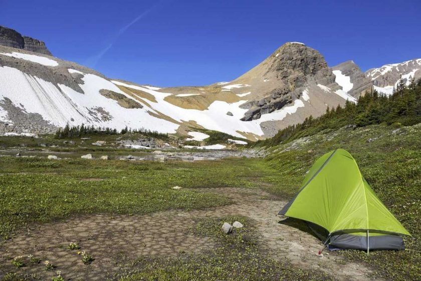 A green tent pitched in the wilderness in front of snow-capped mountains