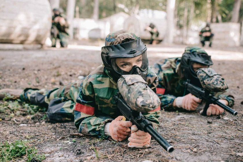 Two people playing paintball in a prone position wearing goggles and other paintball safety equipment
