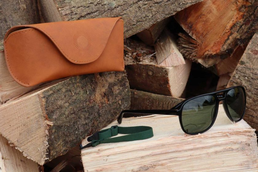 The Vallon Howlin' sunglasses on a wood pile with case and strap