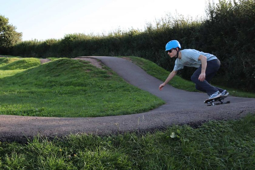 Skateboarding on a pump track while wearing the Vallon Howlin' sunglasses