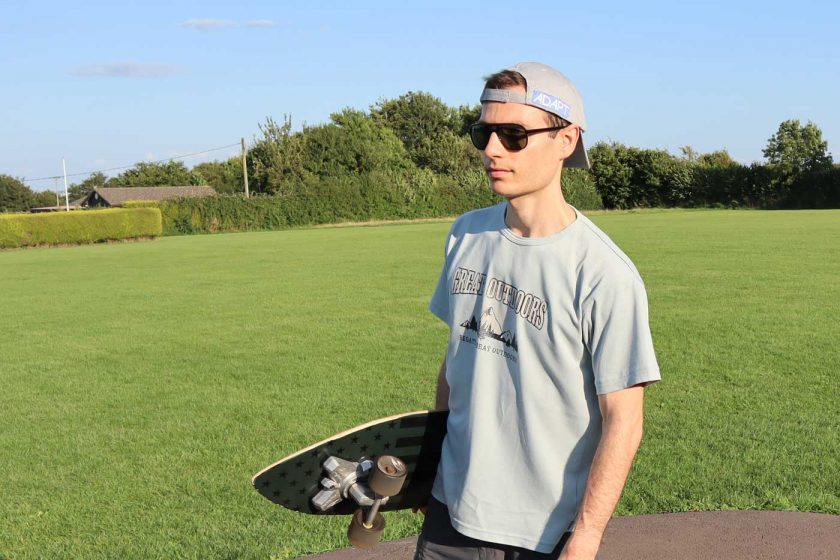 Holding a SwellTech Hybrid surfskate skateboard while wearing the Vallon Howlin' sunglasses