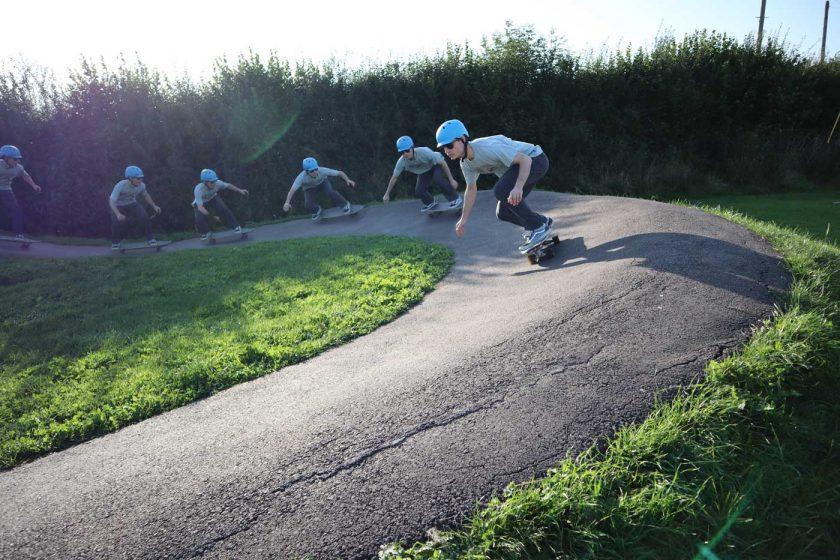 Performing a backside carve on a SwellTech Hybrid surfskate skateboard on a pump track