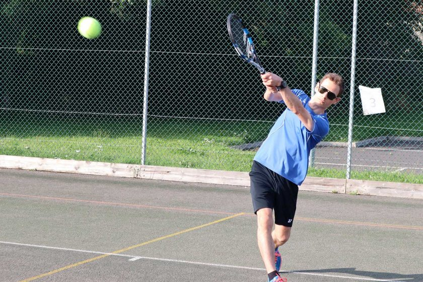 Playing a backhand tennis shot on an outdoor tennis court while wearing the Vallon Howlin' sunglasses