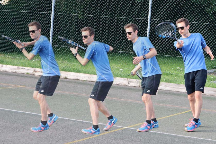 Playing a forehand tennis shot on an outdoor tennis court while wearing the Vallon Howlin' sunglasses