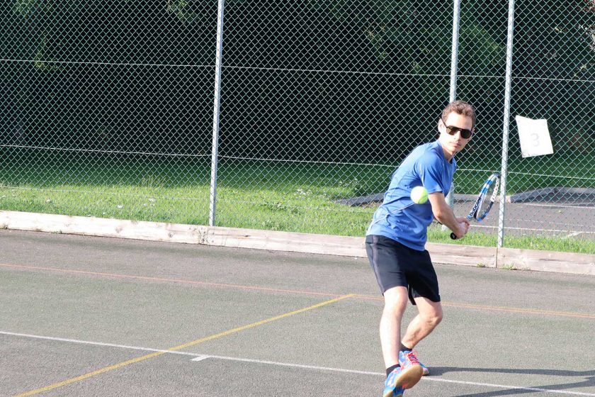 Preparing to play a backhand tennis shot on an outdoor tennis court while wearing the Vallon Howlin' sunglasses