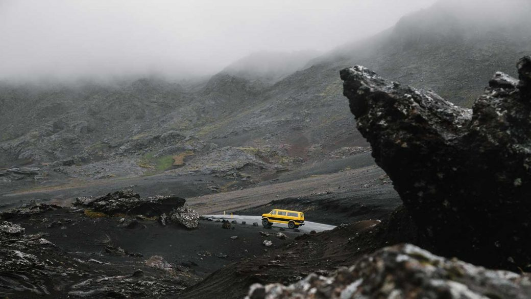 Yellow van driving on a mountain road under an overcast sky