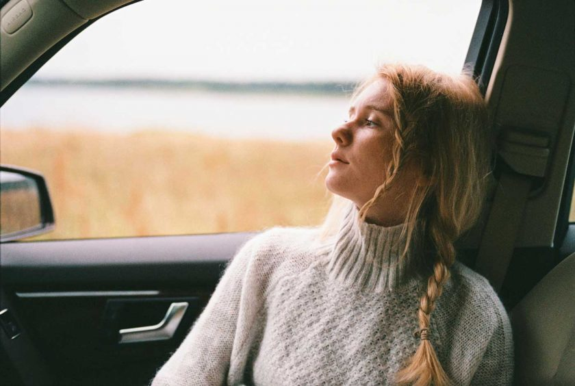 Woman wearing a sweater gazing out of a car window