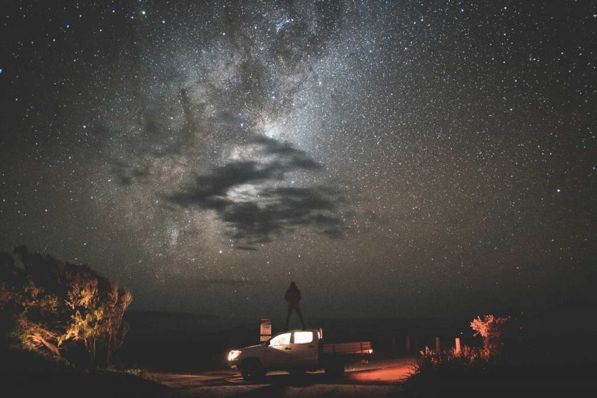 Traveller standing on top of a pickup truck under a starry night sky