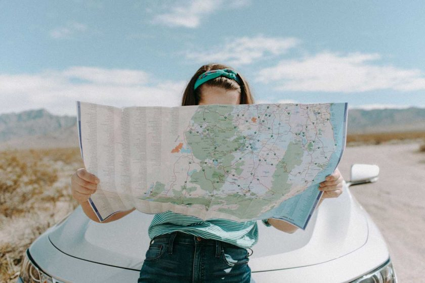 Woman sat on car bonnet reading a map