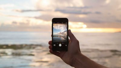 Person taking a photo of a sunset using a smartphone for social media