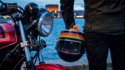 Motorcyclist holding a vintage full-face motorcycle helmet