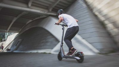 Man riding a kick scooter to work in order to beat the traffic and not be late
